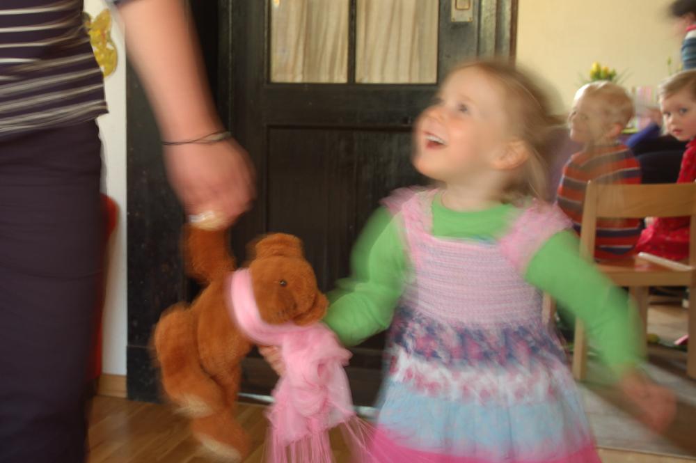 Kind und Erzieherin tanzen mit Teddy im Kinderladen des Ökohaus e.V.